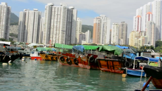 hong kong china aberdeen from boat in water of reclaimed land with skyscraper condos and old ships and boats - aberdeen hong kong stock videos & royalty-free footage