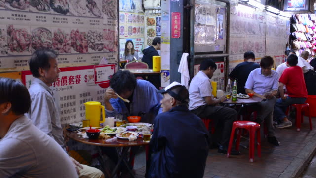 hong kong china kowloon woosung street locals eating chinese food on the street restaurant being social and talking - chinese food stock videos & royalty-free footage