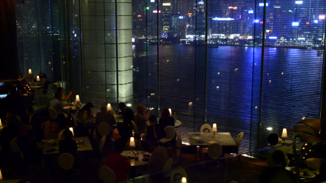 Hong Kong China Peninsula Hotel Felix Bar at night exclusive expensive restaurant with glass and city harbour at night at window