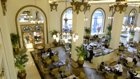 vidéos et rushes de hong kong china  peninsula hotel high tea in lobby of exclusive hotel busy expensive - palace