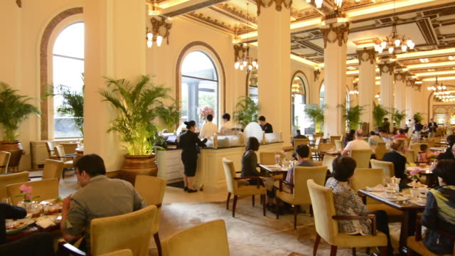 hong kong china  peninsula hotel high tea in lobby of exclusive hotel busy expensive - ホテル点の映像素材/bロール