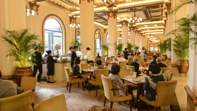 hong kong china  peninsula hotel high tea in lobby of exclusive hotel busy expensive - inside of stock videos & royalty-free footage