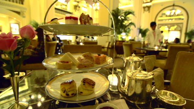 hong kong china peninsula hotel lobby excclusive high tea with tea afternoon tea of cakes and finger sandwichs at table - アフタヌーンティー点の映像素材/bロール