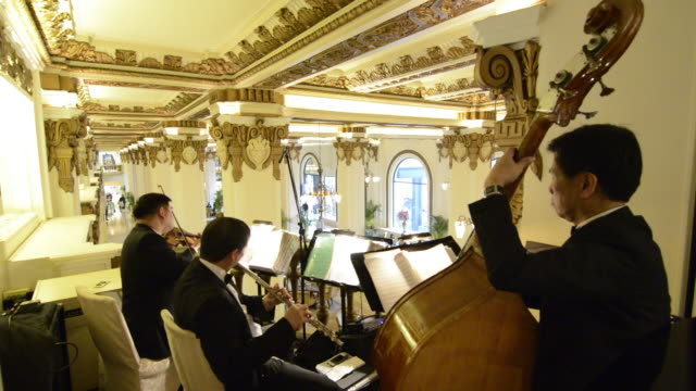 hong kong china  peninsula hotel orchester playing at high tea in exclusive hotel from above lobby with music - アフタヌーンティー点の映像素材/bロール