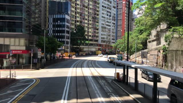 hong kong cityscape - tram moving island east tin hau - hong kong island stock videos & royalty-free footage