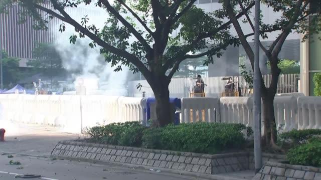 hong kong general strike causes massive disruption as protests continue; hong kong: legislative council complex: ext long shot riot police firing... - tear gas stock videos & royalty-free footage