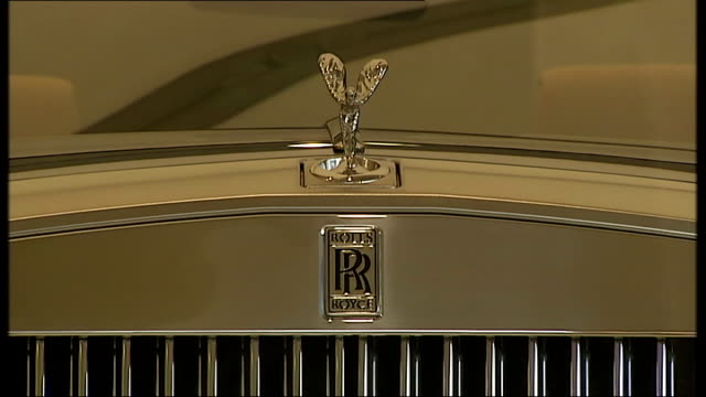 stockvideo's en b-roll-footage met high-rise buildings / rolls royce showroom; ext rolls royce car showroom/ customer talking to saleswoman - seen from outside - toonzaal
