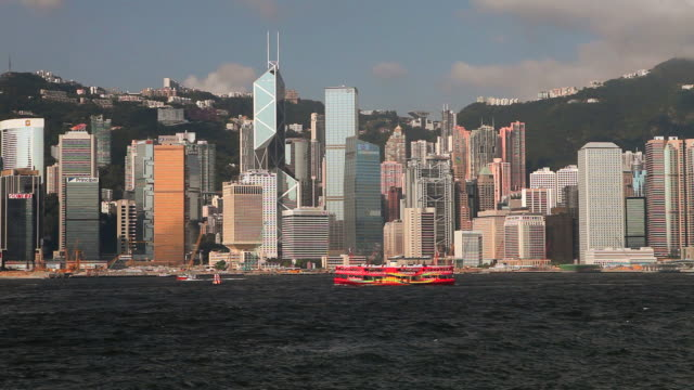 hong kong island skyline (admiralty & central) and red passenger boat in harbour - bank of china tornet hongkong bildbanksvideor och videomaterial från bakom kulisserna