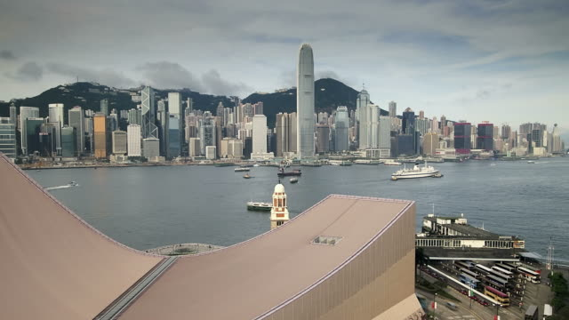 T/L Hong Kong Island skyline, boats in harbour, Cultural Centre roof and Star Ferry Pier in foreground, from Tsim Sha Tsui, Kowloon