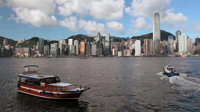 hong kong island skyline, pleasure boat in harbour in foreground - hong kong island stock videos & royalty-free footage