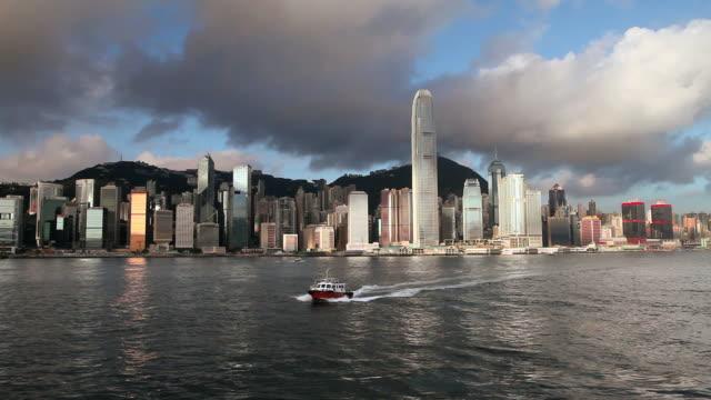 hong kong island skyline, speedboat crosses harbour diagonally to camera - hong kong island stock videos & royalty-free footage