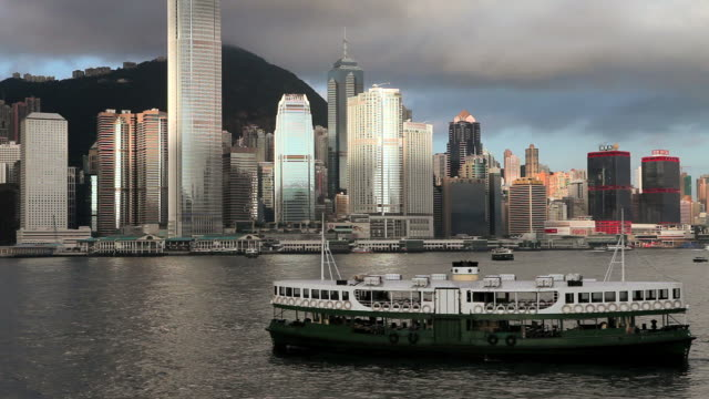 hong kong island skyline, star ferry goes left to right in harbour - star ferry stock videos & royalty-free footage