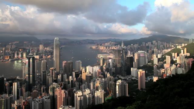 hong kong, pan across city and harbour, high angle from victoria peak, mount austin,, hong kong island across to kowloon. - bank of china tornet hongkong bildbanksvideor och videomaterial från bakom kulisserna