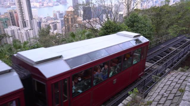 香港のピークトラムは、斜面を下って駅を出ます - 路面軌道点の映像素材/bロール