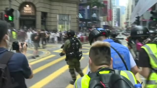 hong kong police fire pepper ball rounds at protesters in the city's commercial district ahead of a debate in the legislature over a law that bans... - demonstrant stock-videos und b-roll-filmmaterial
