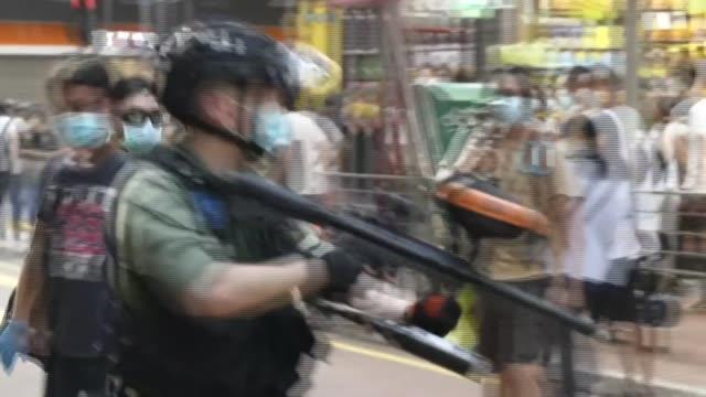 vídeos y material grabado en eventos de stock de hong kong police fire pepper balls and raise warning flags as protesters gathered in mongkok, a busy residential and shopping neighbourhood - manifestante