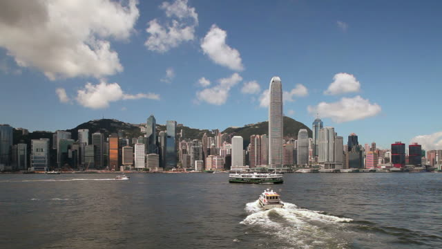 hong kong; speed boat moves away from camera to skyline - スターフェリー点の映像素材/bロール