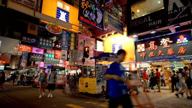 hong kong street scene with neon signs at night - bancarella video stock e b–roll