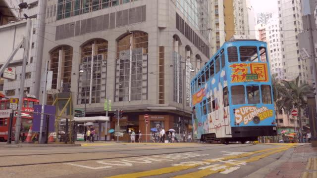 vídeos de stock e filmes b-roll de hong kong tram approaches and passes camera along a turn - linha do elétrico