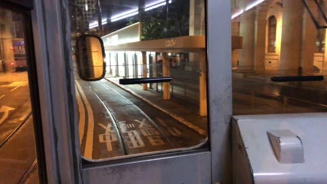 vídeos de stock, filmes e b-roll de bonde de hong kong que move o edifício central de legco na noite dourada - ilha de hong kong