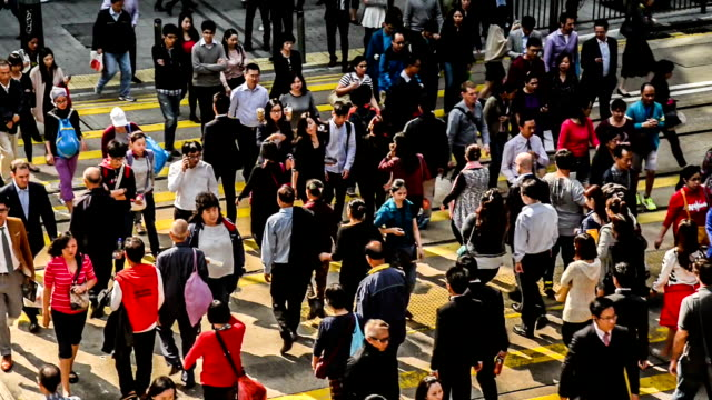 hong kong,china-nov 14,2014: the pedestrians cross the street at the downtown of hong kong,china - central district hong kong stock videos and b-roll footage
