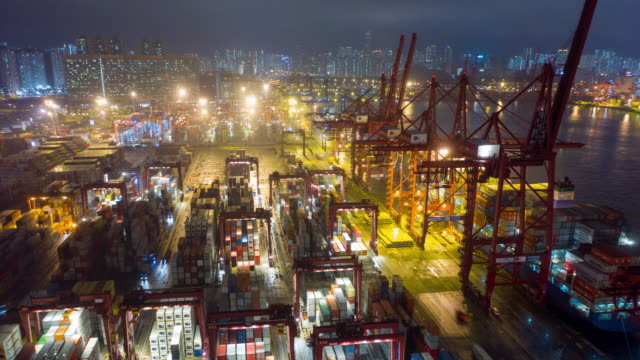 vídeos de stock e filmes b-roll de hongkong aerial drone hyper time lapse at container terminals and stonecutters bridge at night - transporte de mercadoria
