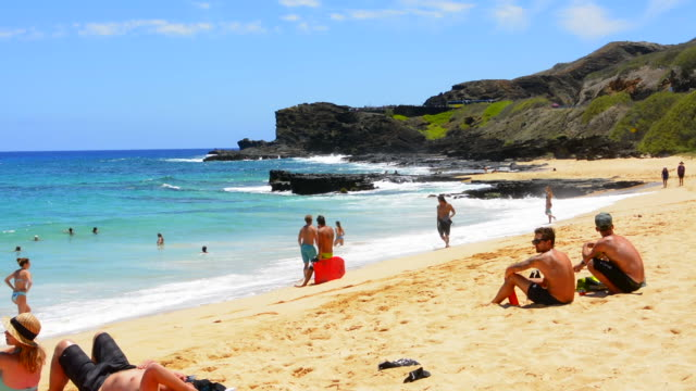 honolulu hawaii oahu beach with tourists at sandy beach park on south oahu relax - stare in piedi video stock e b–roll