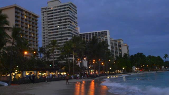 honolulu hawaii oahu waikiki beach beautiful sunset with hotels on beach, come to hawaii - pantaloncino da bagno video stock e b–roll