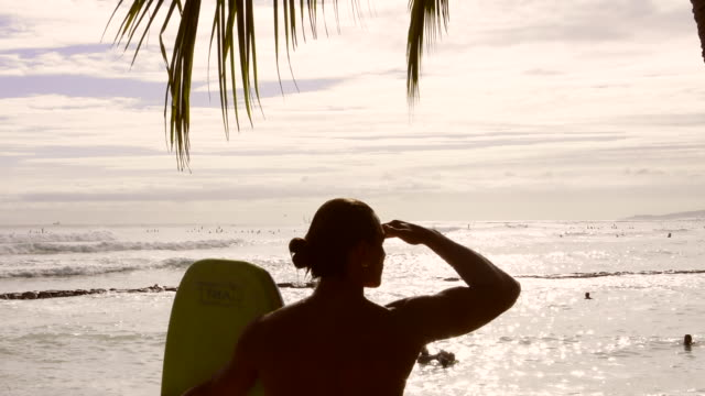 honolulu hawaii oahu waikiki beach surfer looking out over water silhouette over waves and surfboard - 手をかざす点の映像素材/bロール