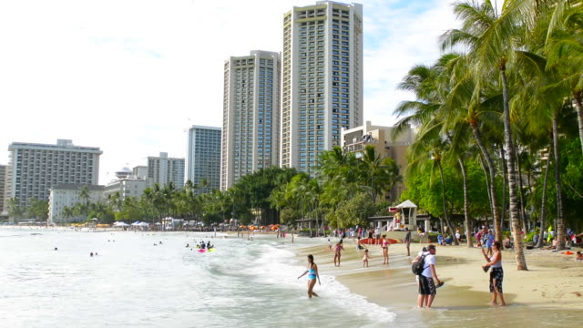 honolulu hawaii oahu waikiki beach with tourists on wonderful beach with water and sand - 打ち寄せる波点の映像素材/bロール
