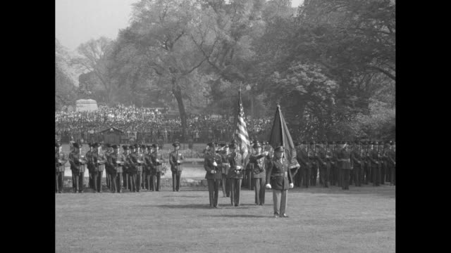 honor guard and numerous soldiers snap to attention, funeral cortege moves left behind them, and the men watch / caisson pulled by white horses... - funeral stock videos & royalty-free footage