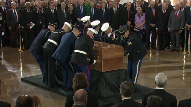a honor guard sets in place a casket carrying the late reverend billy graham on the lincoln catafalque prior to a memorial service and lying in honor... - 光栄点の映像素材/bロール