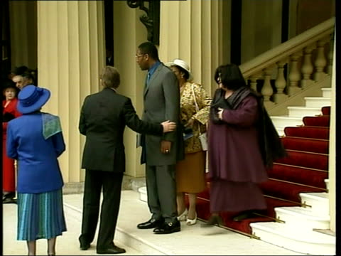 vídeos de stock e filmes b-roll de honours - lenny henry recieves cbe; england: london: buckingham palace: ext lenny henry cbe down steps out of palace with wife dawn french and his... - lenny henry