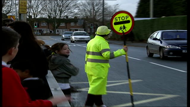 lollypop lady stella muncaster receives mbe muncaster crossing road pull out children crossing road dissolve to - lollypop lady stella muncaster stock videos & royalty-free footage
