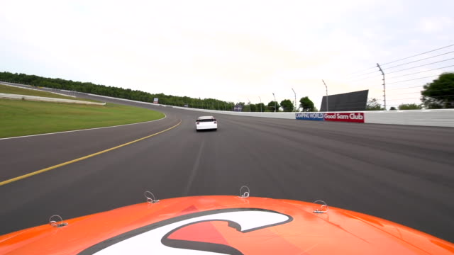 Hood Mount POV. Orange stock car passes green car and moves in behind white car on race track straightaway.