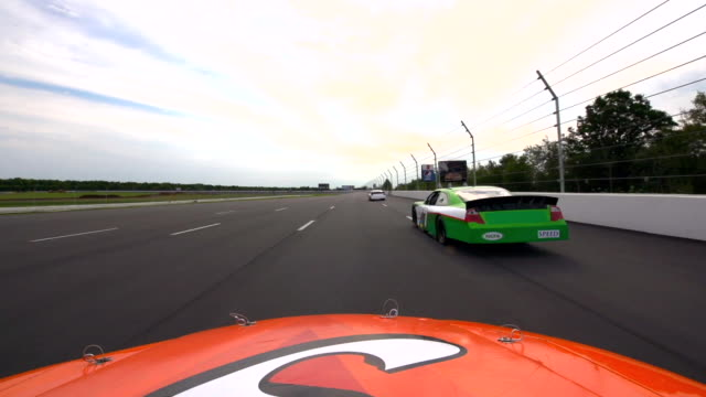 hood mount pov. orange stock car passes red car in the curve and speeds away. - motorsport stock videos & royalty-free footage