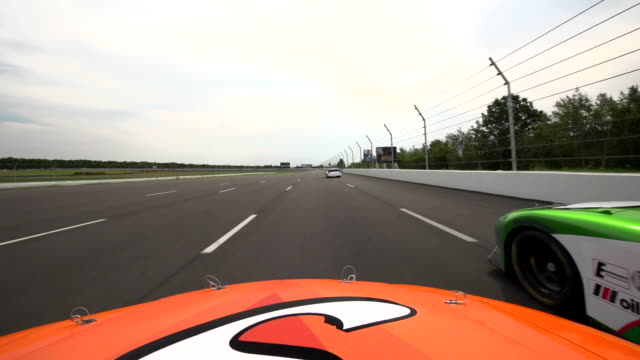 hood mount pov. orange stock car speeds past red car on race track straightaway. - overtaking stock videos and b-roll footage
