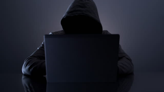 hooded hacker. cyber crime. - computer hacker stock videos & royalty-free footage
