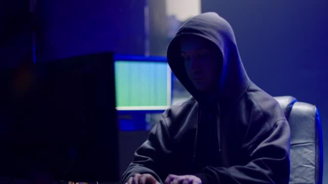 vidéos et rushes de hooded hacker travaillant sur ordinateur - média