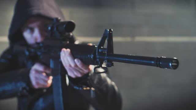 hooded man aimimg machine gun towards camera. close up on face - machine gun stock videos & royalty-free footage