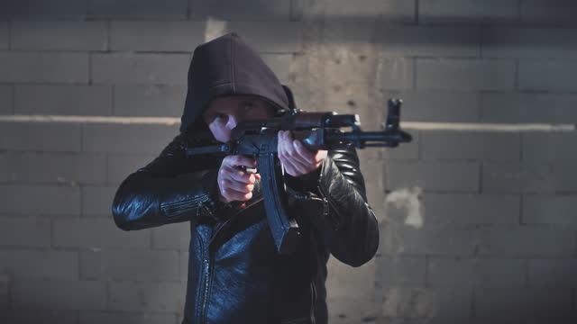 hooded man aimimg machine gun towards camera - machine gun stock videos & royalty-free footage
