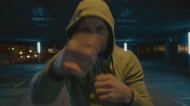 vidéos et rushes de slo mo hooded homme ombre boxe sur un parking la nuit - boxe
