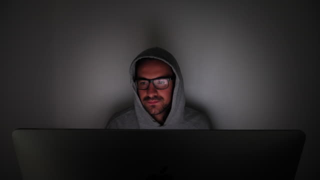 hooded man working on a computer at night, sips coffee. lockdown. - only young men stock videos & royalty-free footage
