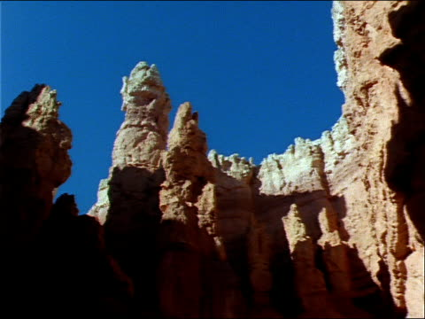 vídeos de stock e filmes b-roll de hoodoos in bryce canyon cast shadows on surrounding rock. - pináculo formação rochosa