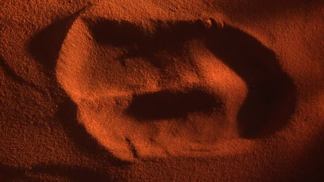 vidéos et rushes de a hoofed footprint in red sand becomes blurred as time passes. available in hd. - sable