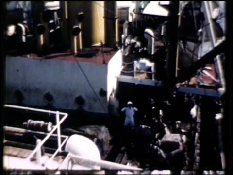 vidéos et rushes de hook, rope & crane lifting cargo of rubber latex bales onto cargo ship, loading, fade to black. harbel, liberia - fondu de fermeture