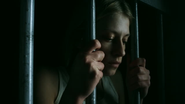 hopeless women holding bars and looking through - claustrophobia stock videos & royalty-free footage