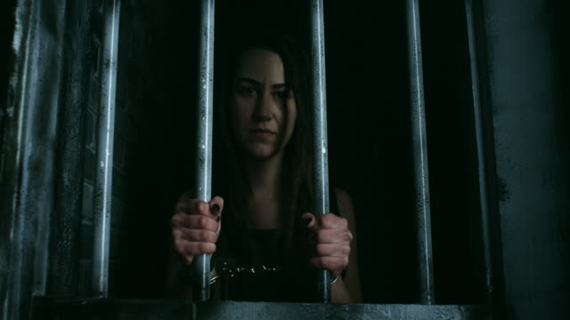 hopeless women with handcuffs holding bars and looking through - women prison stock videos & royalty-free footage