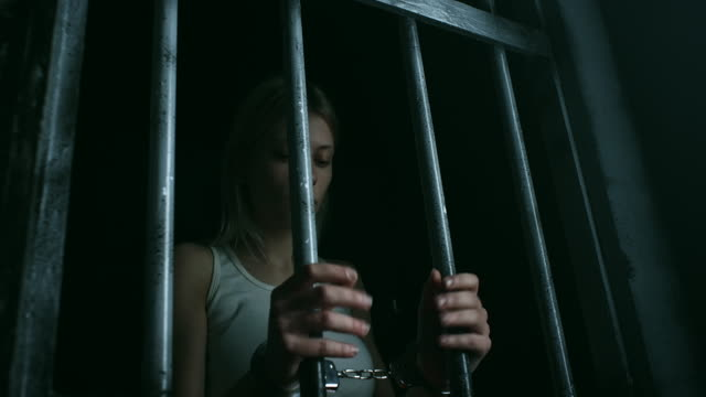 hopeless women with handcuffs holding bars and looking through - claustrophobia stock videos and b-roll footage