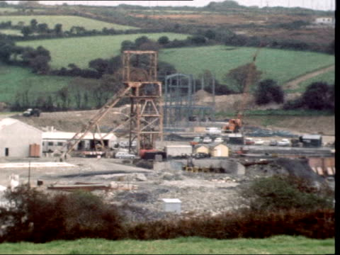 hopes of industrial revival on tin mining:; england: cornwall: ext southgate sof: mine ruins in b/g: pan ruins of tin mine l-r: old mine wheel; full... - tin mine stock videos & royalty-free footage